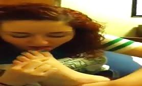 Curly hair teen sucks her own toes